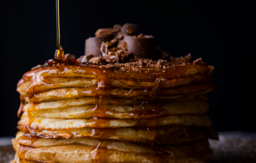 maply syrup being poured on pancakes