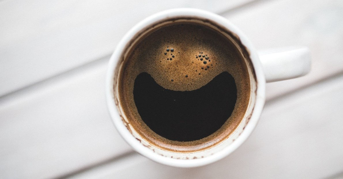 Image of a cup of coffee with a smiley face in the froth